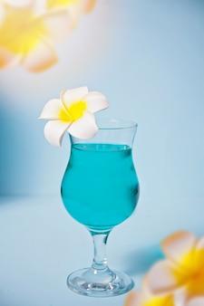 プルメリアフランジパニの花とガラスのエキゾチックなトロピカルブルーキュラソーカクテルドリンク。