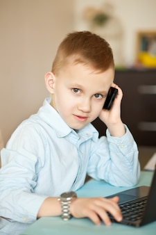 ノートパソコンとワークスペースのオフィスデスク。テーブルに座っているかわいいビジネス少年。子供のオンライン学習。