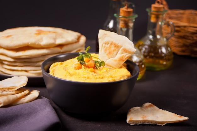 Традиционная закуска хумус с нутом подается со свежим лавашом и зеленью.