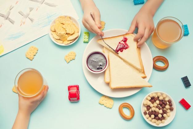 Два ребенка дети едят бутерброды закуски и печенье и пить яблочный сок на столе. вид сверху.
