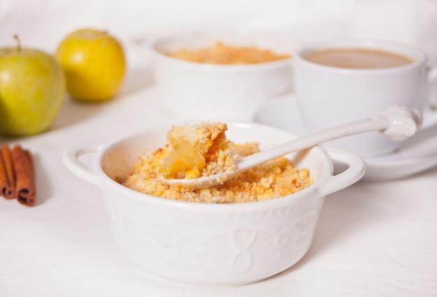 Вкусное домашнее яблоко крошит десерт на белой поверхности.