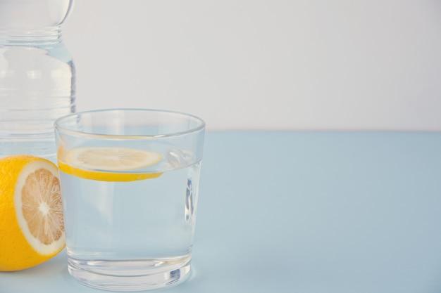 青いテーブルの上のレモンと水