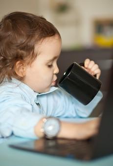 ノートパソコンとワークスペースのオフィスデスク。テーブルに座って、マグカップのコーヒーを飲んでかわいいビジネス少女。子供のオンライン学習。オンライン教育の遠隔学習。