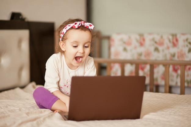 ベッドの上に座って、デジタルタブレットのラップトップノートブックを使用してかわいい女の子。友人や両親にオンラインで電話をかける。