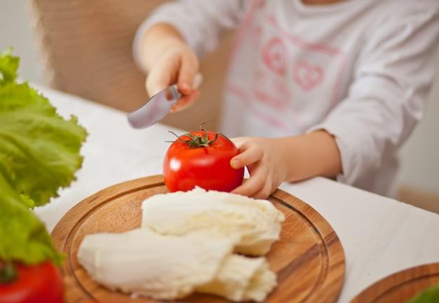 Ребенок ребенок готовит овощи для салата в домашней кухне. здоровое питание.