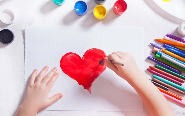 子供は紙に色の塗料で赤いハートを描画します。