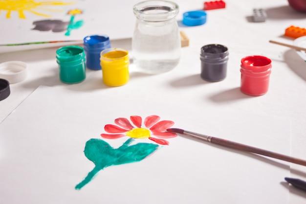 紙に色の絵の具で描く花。