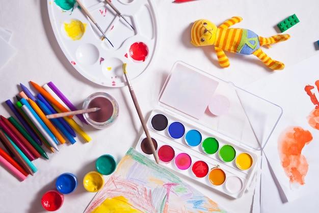ブラシ、塗料、ガッシュ、テーブルの上にカラフルな鉛筆。子供の創造性。創造的な混乱。上面図。
