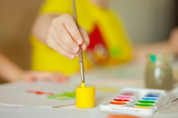 紙に色の絵の具で描く子供たち。