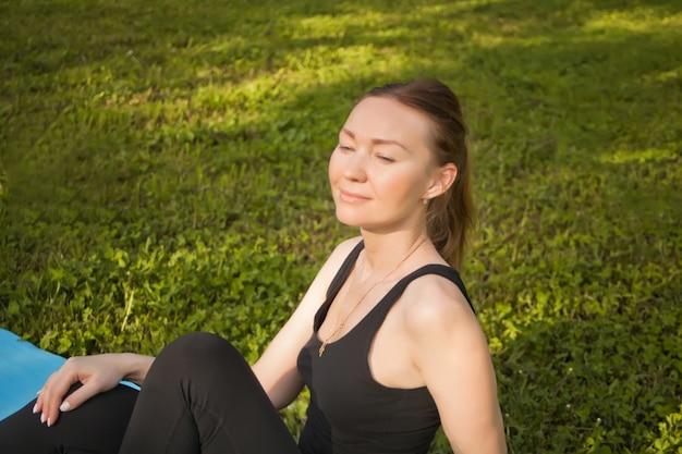 スポーツマットの上に座って、トレーニング後にリラックスできるアクティブなスポーティな女性