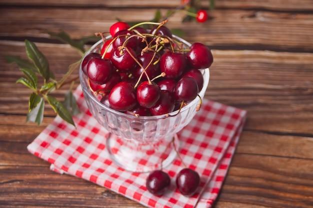 素朴な木製のテーブルの上にボウルに新鮮な熟した有機甘いチェリー。