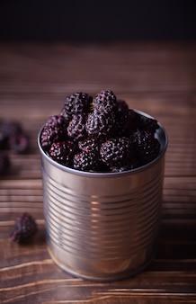 素朴な木製のテーブルに缶の新鮮な熟した有機ブラックベリー