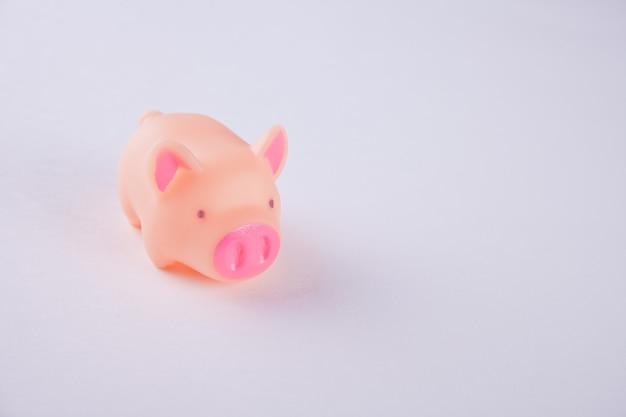 青い背景にピンクのプラスチック豚