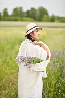 牧草地の枝編み細工品バスケットでライラックの花を摘む帽子の女。