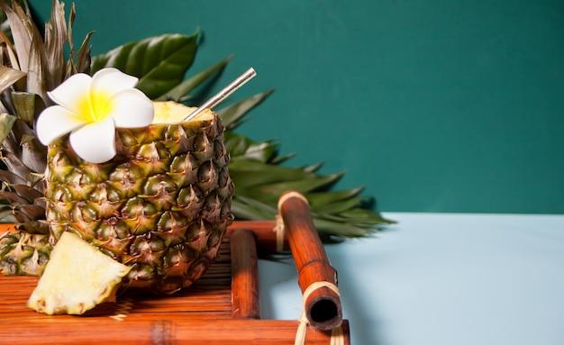 プルメリアフランジパニの花と装飾用のヤシの葉が入ったパイナップルのエキゾチックなトロピカルカクテルドリンク。