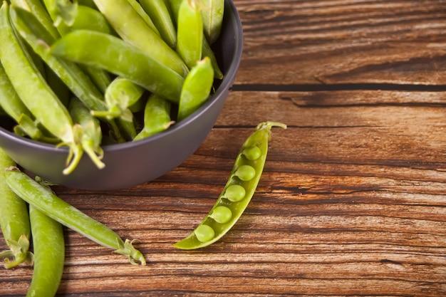 木製のボウルに有機の新鮮なグリーンピースとエンドウ豆の鞘