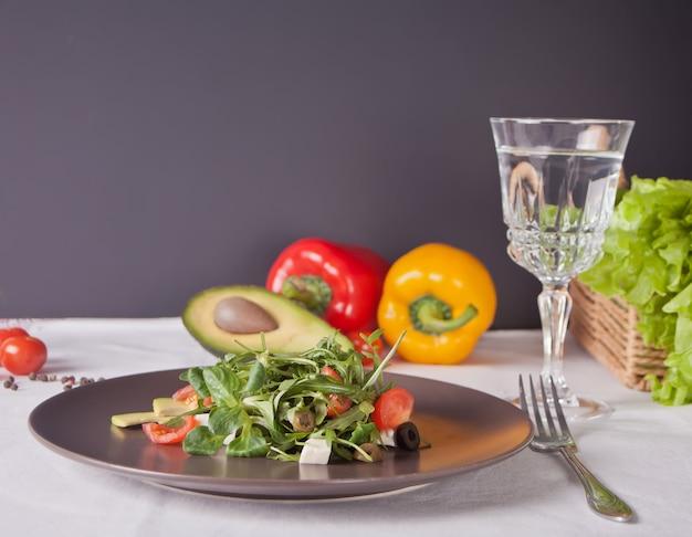 新鮮な野菜サラダプレートと新鮮な水とガラス