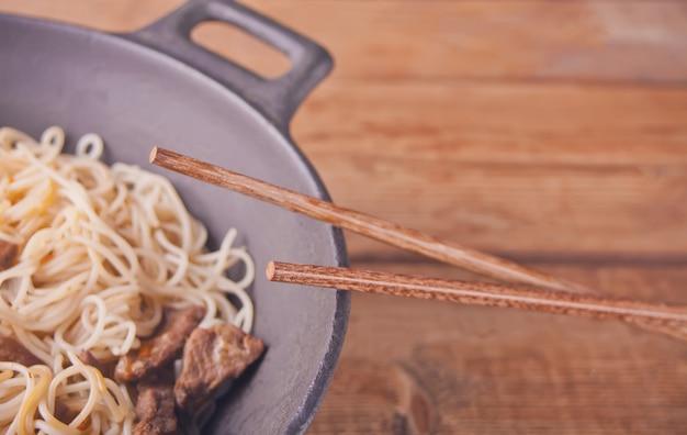 牛肉、箸、素朴な木製の背景を持つ中華鍋で野菜とアジアンヌードル。アジアンスタイルのディナー。中華麺