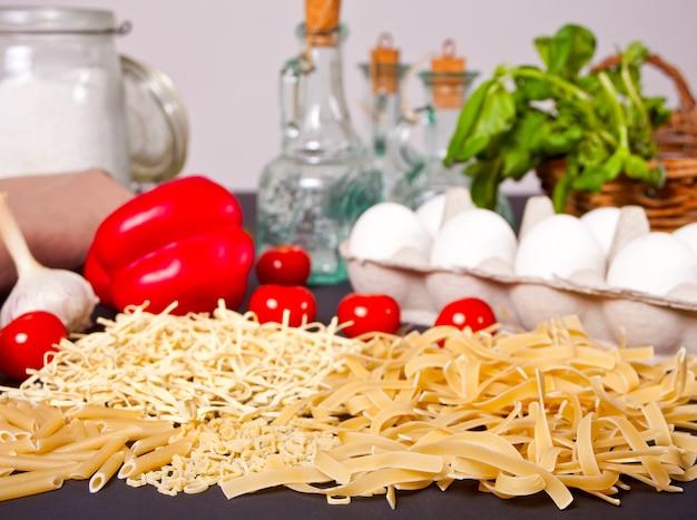 Макароны и овощи на черном столе