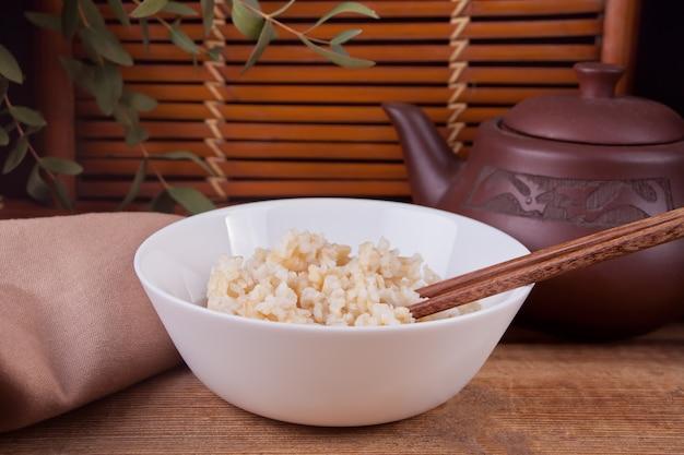 木製の背景にお箸で白いボウルに玄米を調理しました。