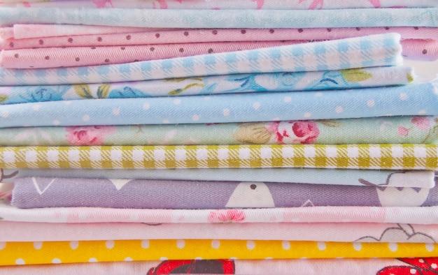 木製のテーブルの上の異なる色の布で新しい布のスタック
