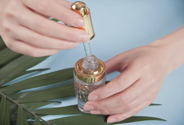 Женская рука держит пипетку с жидкостью, в которой видны золотые частицы. капля капает в прозрачной бутылке.