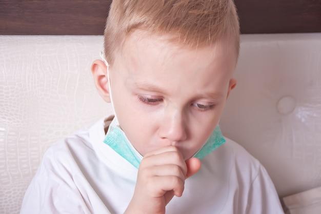 自宅のベッドで咳に苦しんでいる病気の少年