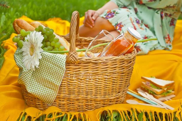 食品、果物、ワイングラス、黄色いカバーの上に花のピクニックバスケットのクローズアップ