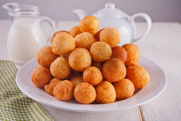 白い背景の上の皿に焼きたての自家製カッテージチーズドーナツの小さなボール。