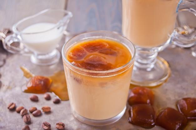 アイスキューブとコーヒー豆のテーブルの上にアイスラテコーヒー。