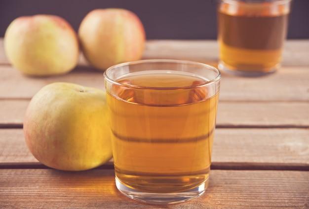 リンゴジュースと木製のテーブルの上のリンゴ。