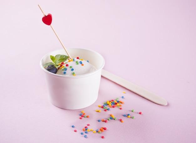 Ванильное мороженое с листьями мяты, клубникой и черникой на розовом