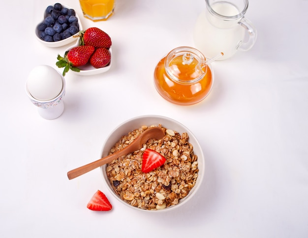 白いテーブルの上のイチゴ、蜂蜜、牛乳とミューズリー。平らに置きます。