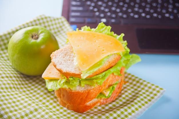 Обед с бутербродом и зеленым яблоком и ноутбук на столе.