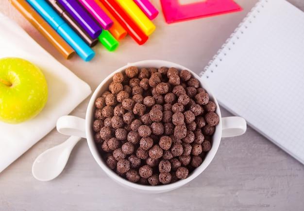 健康的な朝食のための灰色のテーブルの上の乾燥チョコレートボールシリアルと青リンゴのボウル