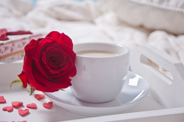 Закройте чашку чая с красной розы и маленькие конфеты сердцах на столе