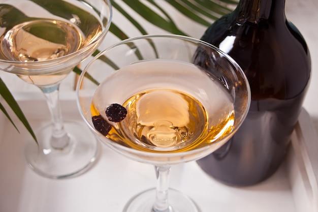 グラス、白の木製トレイにボトルの白ワイン。