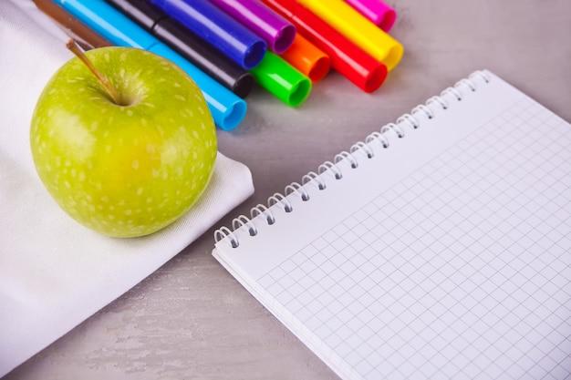 カラフルなサインペン、ノート、灰色の背景に青リンゴ
