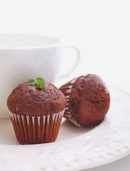 白いプレート、白い背景の上の紅茶のカップとチョコレートのカップケーキ