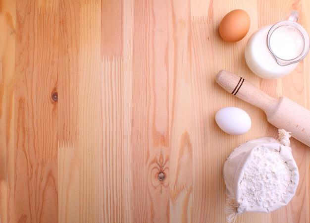 Яйца мука молочная и венчик на фоне дерева