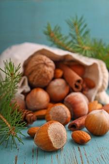 ナッツとシナモンのクリスマスバッグは、青色の背景にスティックします。