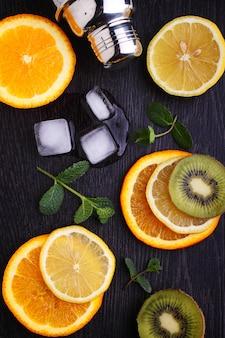 レモン、オレンジ、キウイ、黒の背景にミント。レモネードのための原料