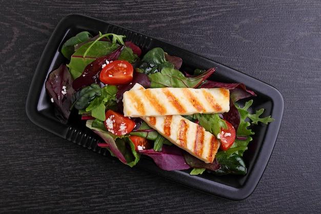 Зеленый салат с жареным сыром халуми на темном столе, вид сверху.