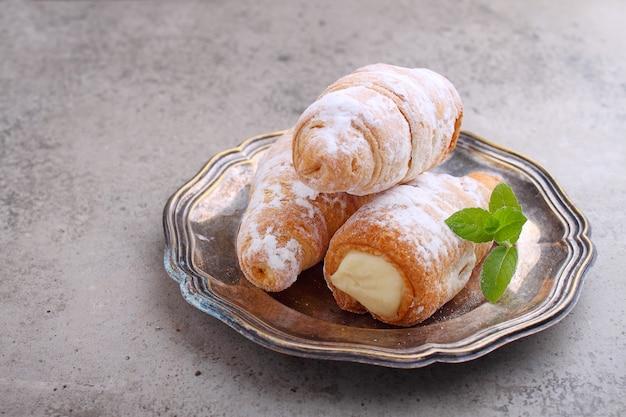 砂糖粉末とミントの葉で飾られたクリームが入った「ストロー」ケーキ