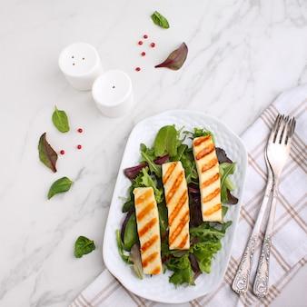 Зеленый салат с жареным сыром халуми на белой тарелке