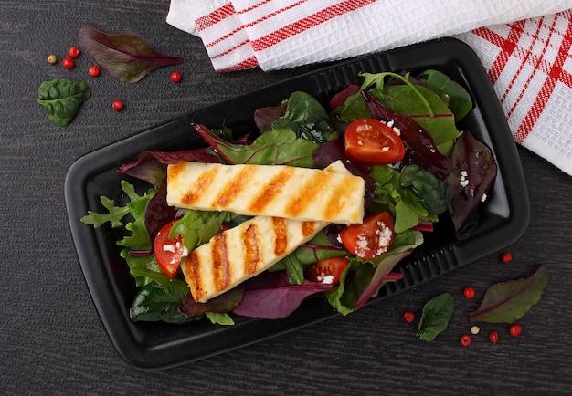 Зеленый салат с жареным сыром халуми на черной тарелке