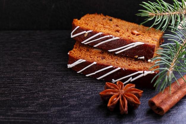 アイシング、トウヒの枝、シナモンスティック、黒い背景にスターアニスで飾られたレーズンとジンジャーブレッド(蜂蜜ケーキ)