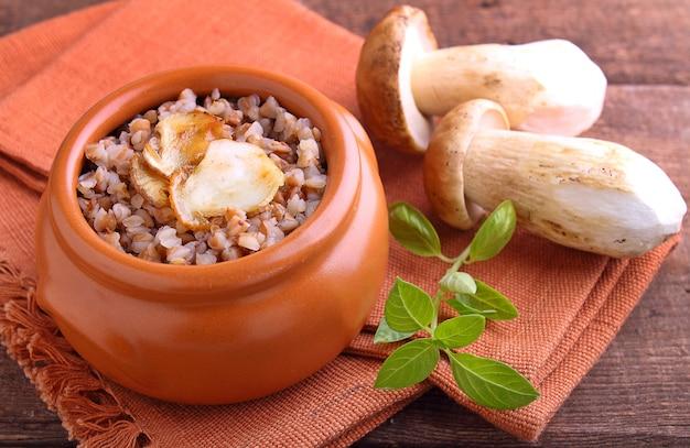 木製の背景に粘土ボウルに白いキノコのそば米雑炊