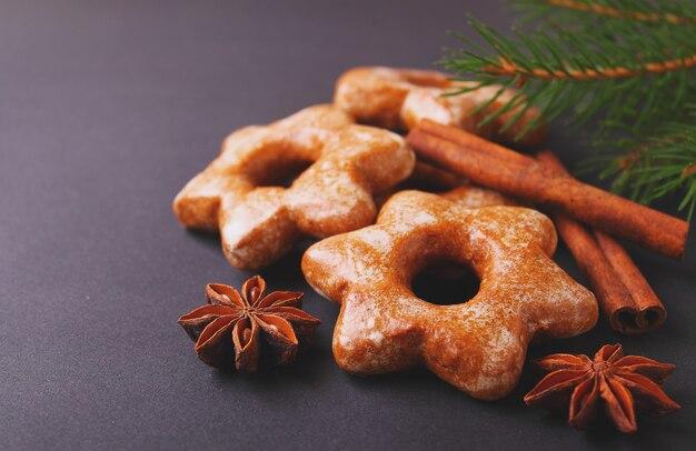 スパイス(シナモン、アニス)、小ぎれいなな枝を持つクッキー。黒の背景