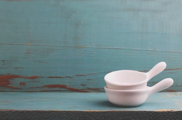 Белые блюда для молока в старом синем деревянном фоне